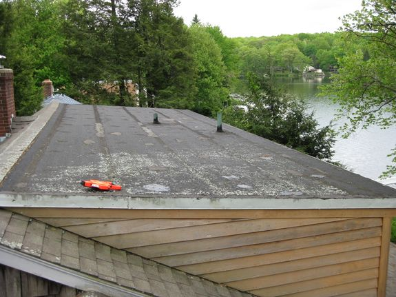 This lake front home in Andover, Connecticut has a rolled asphalt roof that has been patched multiple times and still leaks.