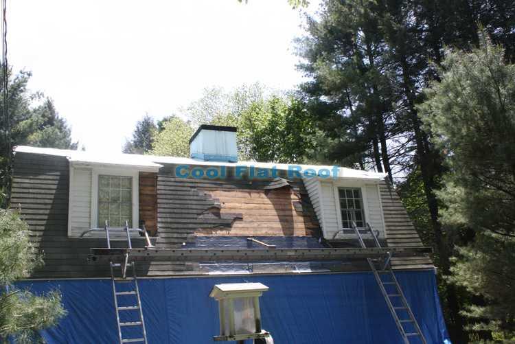 Tearing off old asphalt shingles roof in Wayland MA