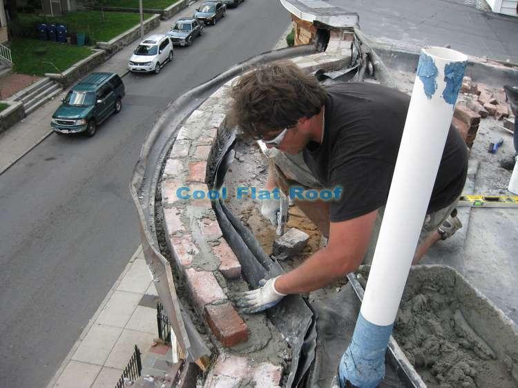 Installaing bricks on parapet walls, on a flat roof in Boston, MA