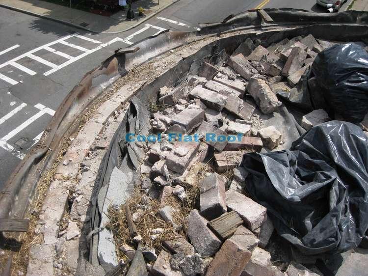 Removing bricks from parapet walls to repair mortar.