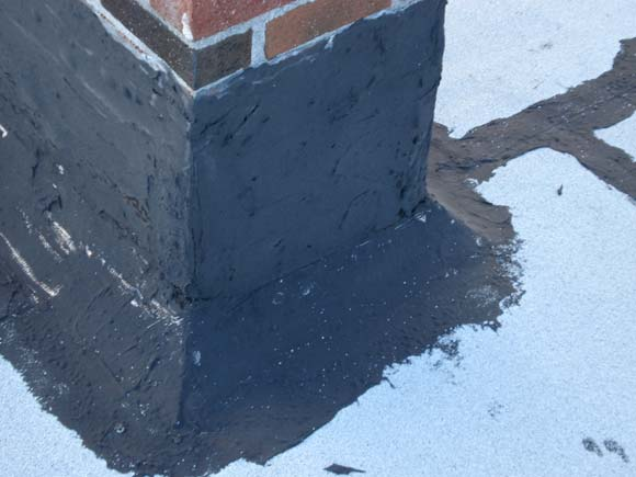 Flat roof chimney flashing used tar and reinforced fabric. After 7 years, tar dried up and began to crack, letting water penetrate the roof.